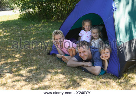 Caucasian family looking out of tent at campsite - Stock Photo