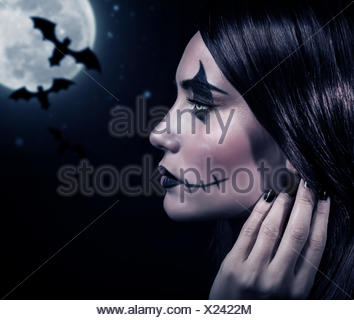Side view of terrifying witch in Halloween night, bats on full moon background, portrait of werewolf on scary dark night, horror concept - Stock Photo
