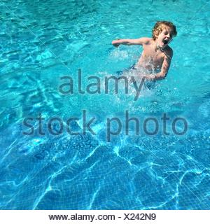 High Angle View Of Boy Playing In Swimming Pool - Stock Photo