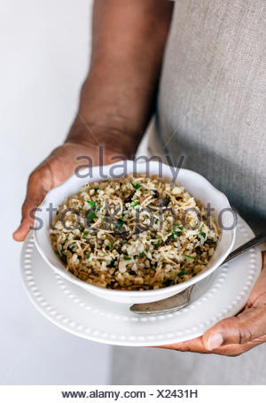 A bowl of bulgur pilaf mixed in with lentils and fresh herbs are in the hands of a man wearing an apron. - Stock Photo