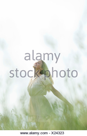 Young woman in field of tall grass, standing with head back and eyes closed - Stock Photo