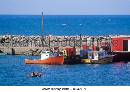 Fisherman rowing to wharf at Port Morian Harbour, Cape Breton, Nova Scotia, Canada - Stock Photo