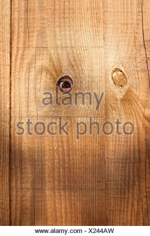 somebody peeping through a hole in the fence - Stock Photo