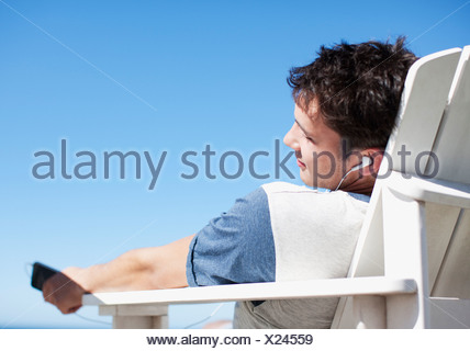 Man sitting in deck chair listening to headphones with eyes closed - Stock Photo