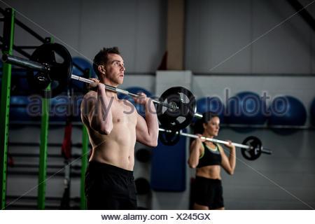 Man and woman lifting barbell - Stock Photo