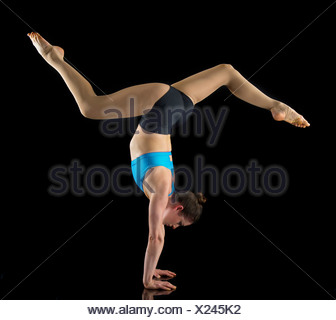 Acrobat performing handstand in front of black background - Stock Photo