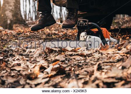 Man in boots and chainsaw on autumn forest floor - Stock Photo