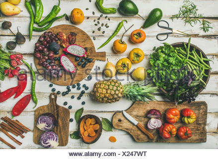 Helathy raw vegan food cooking background. Flat-lay of Fresh fruit, vegetables, greens and superfoods on boards over white wooden table, top view. Cle - Stock Photo