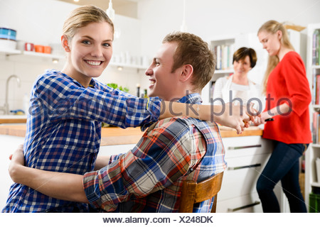 Young couple in kitchen with woman and teenage girl - Stock Photo