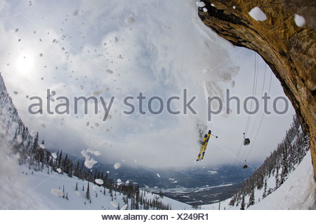 a male skier flys off a cliff at Kicking Horse Resort, Golden, BC - Stock Photo