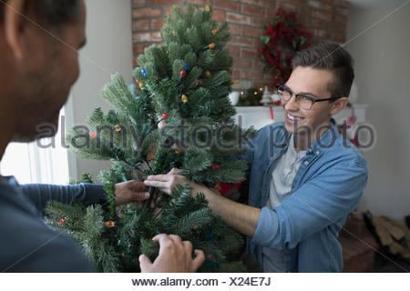 Father and son decorating, assembling artificial Christmas tree in living room - Stock Photo