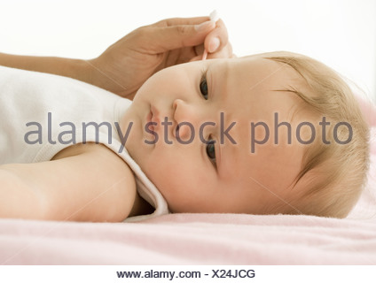 Baby having ear cleaned - Stock Photo