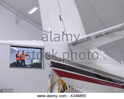 Engineers look out onto jet aircraft - Stock Photo