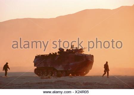 US Marines Walk Alongside an AAV-7 Amphibious Assault Vehicle - Stock Photo