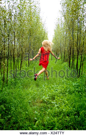 Young woman running in forest - Stock Photo