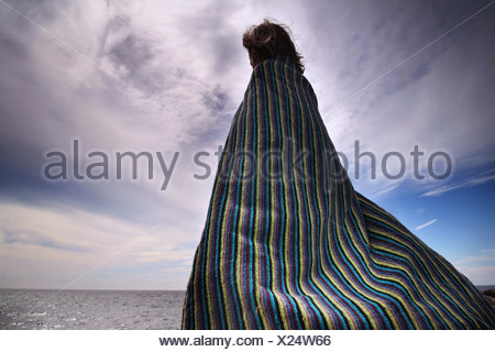 young boy stood on the beach with a towel wrapped around himself - Stock Photo