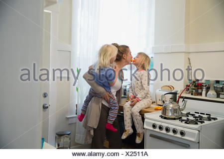 Playful mother and daughters in morning kitchen - Stock Photo