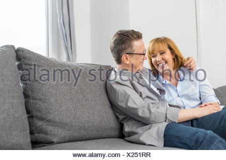 Happy loving couple sitting on sofa at home - Stock Photo