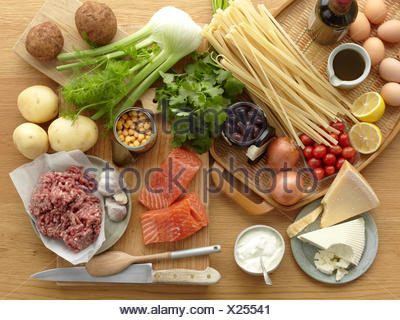 Selection of fresh raw foods with eggs, pasta, herbs, cheese, vegetables, salmon and minced pork - Stock Photo