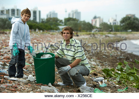 Young male and boy picking up trash on polluted shore - Stock Photo