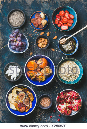 Ingredients for healthy breakfast over dark blue background, top view. Fresh and dried fruit, chia seeds, oatmeal, nuts, honey. Clean eating, vegan, v - Stock Photo
