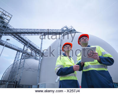 Workers using digital tablet at biomass facility, low angle view - Stock Photo