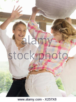 Two sisters having pillow fight - Stock Photo