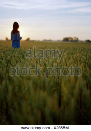 Mid adult woman standing in fields - Stock Photo