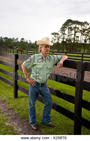 Senior man wearing cowboy hat on ranch leaning on fence - Stock Photo