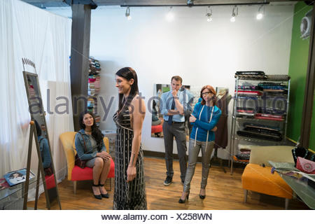 Dressmakers watching customer trying on dress - Stock Photo