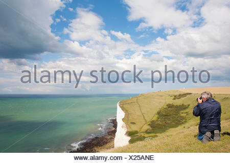 MAN TAKING PHOTOGRAPH OF CHANNEL, WHITE CLIFFS AND NORTH DOWNS - Stock Photo