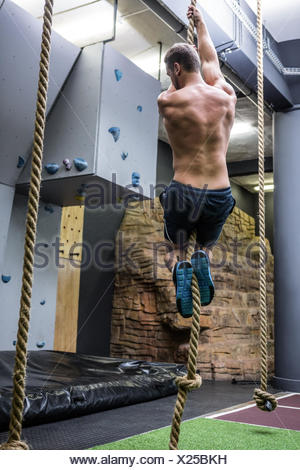 Back view of muscular man doing rope climbing - Stock Photo