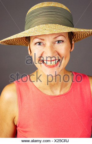 a woman summerly dressed wearing a strawhat, portrait - Stock Photo