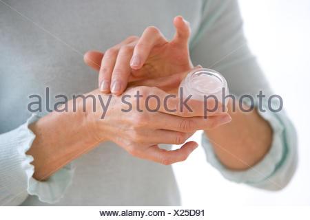 Woman applying moisterizing cream on her hands. - Stock Photo