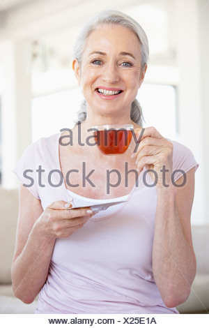 Senior Woman Holding Tea And Smiling At The Camera - Stock Photo