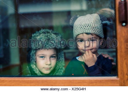 Two boys looking out of a window - Stock Photo
