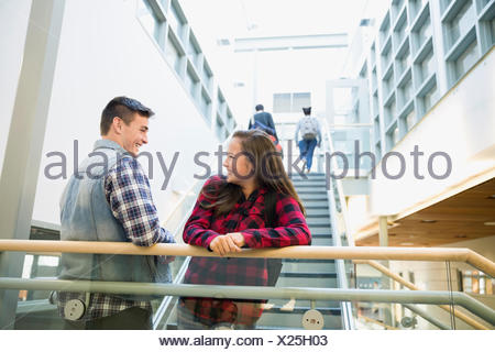 High school student couple talking on stairs - Stock Photo