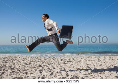 Cheerful businessman jumping on the beach - Stock Photo