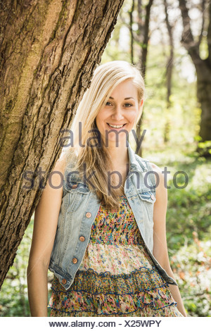 Portrait of young woman leaning against tree in forest - Stock Photo