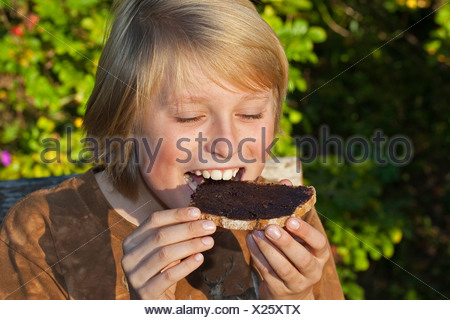 Common hazel (Corylus avellana), boy sitting at the garden table eating a slice of bread with chocolate spread he made of self-collected hazelnuts, cocoa powder, butter and sugar, Germany - Stock Photo