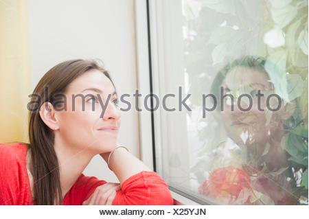 Smiling woman looking through window - Stock Photo