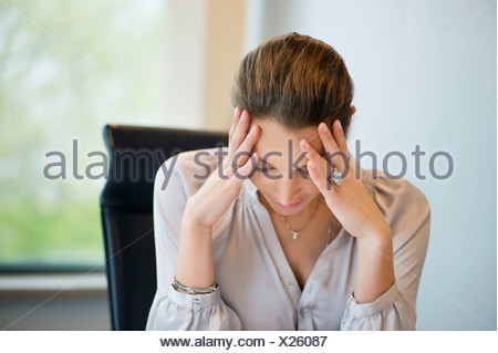 Close-up of a businesswoman suffering from a headache in an office - Stock Photo