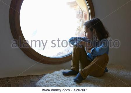 Girl sitting on floor gazing through circular window - Stock Photo