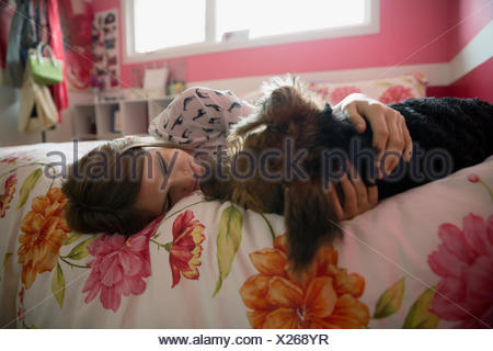Girl cuddling dog face to face on bed - Stock Photo