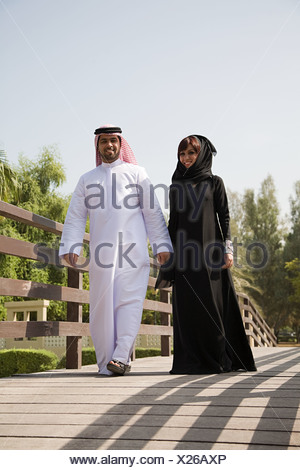 A couple walking along a bridge - Stock Photo