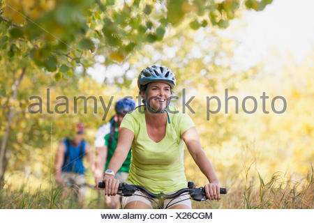 Friends biking on pathway in park. - Stock Photo