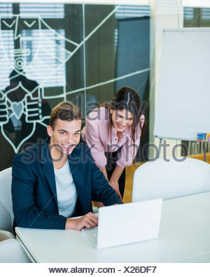 Portrait of smiling young businessman with female colleague using laptop at table in office - Stock Photo