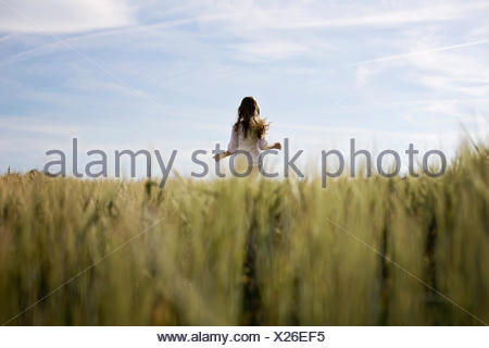 Little girl running in green field - Stock Photo
