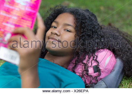 Close up portrait of young girl reading in park - Stock Photo