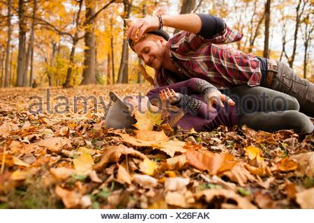 Young couple play fighting with autumn leaves in forest - Stock Photo